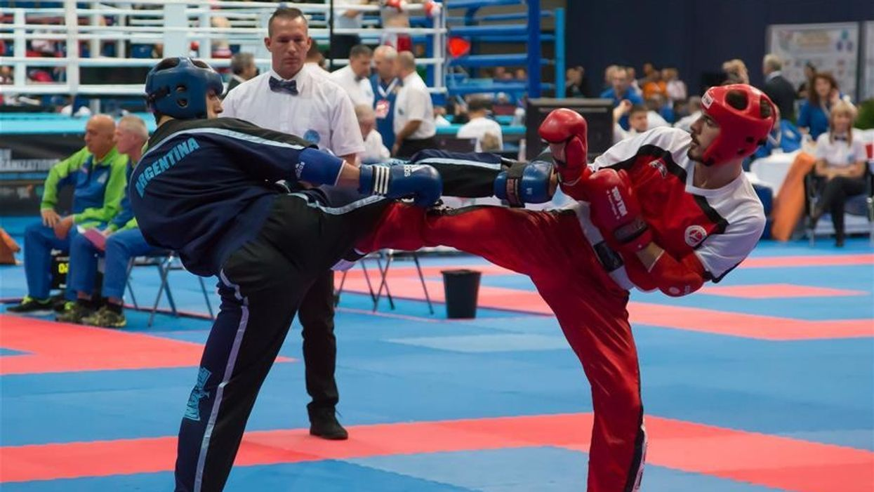 Two point fighters exchanging kicks at a WAKO event.